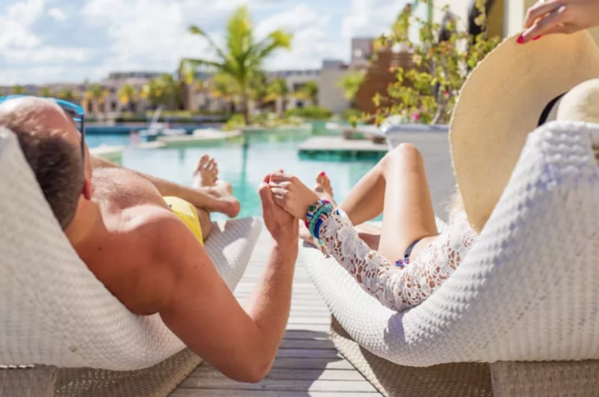 Couple Holding Hands By The Pool