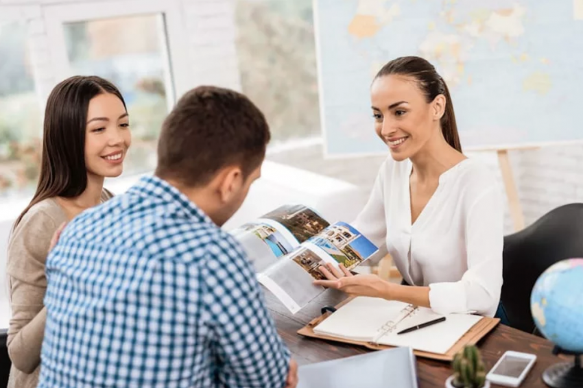 Couple Looking At Brochure With Travel Agent