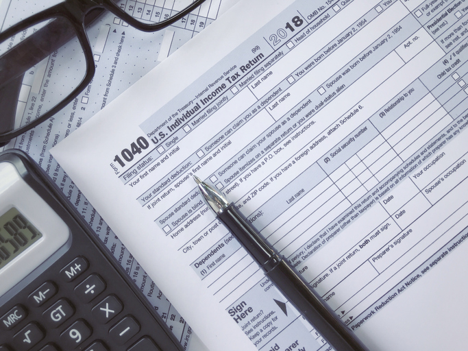 United States federal income tax return IRS 1040 documents, with pen calculator and eyeglasses.